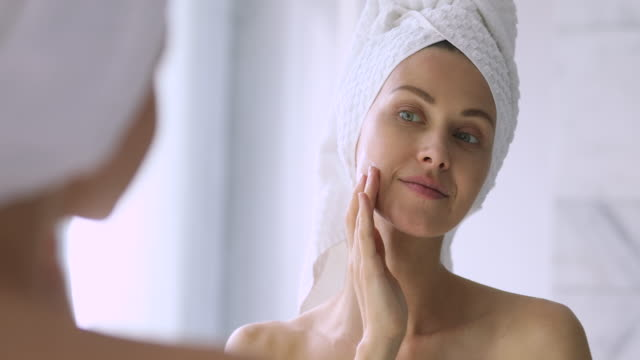 Happy beautiful lady hydrating skin, enjoying daily skincare routine. Close up head shot attractive young woman with bowel on head, applying moisturizing balm creme after morning shower in bathroom. Happy beautiful lady hydrating skin, enjoying daily skincare routine. lip balm stock videos & royalty-free footage