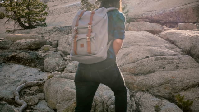 happy beautiful tourist girl with backpack hiking on big rocks exploring sunny yosemite national park forest slow motion - park narodowy yosemite filmów i materiałów b-roll
