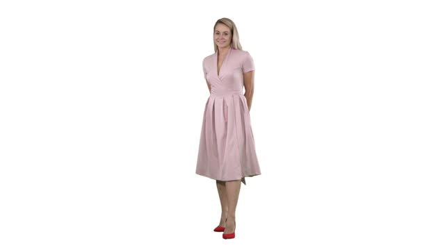 Happy beautiful woman in pink dress posing on white background Full length portrait. Happy beautiful woman in pink dress posing on white background. Professional shot in 4K resolution. 005. You can use it e.g. in your commercial video, business, presentation, broadcast full length stock videos & royalty-free footage