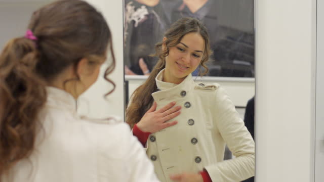 happy beautiful woman in the mirror trying on winter coats video