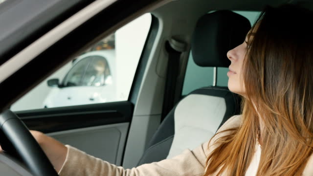 Happy beautiful woman inspects the cabin of modern car video