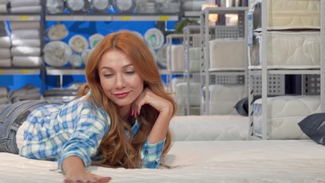 vídeos y material grabado en eventos de stock de feliz hermosa mujer acostada en un nuevo colchón ortopédico en la tienda de muebles - colchón