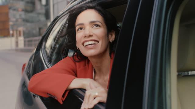 glad vacker kvinna rider på en baksätet på en bil, ser ur det öppna fönstret i förundran i stora staden. resor flicka erfarenhet magin i världen. kameran skott gjort från utanför fordonet. - människohuvud bildbanksvideor och videomaterial från bakom kulisserna
