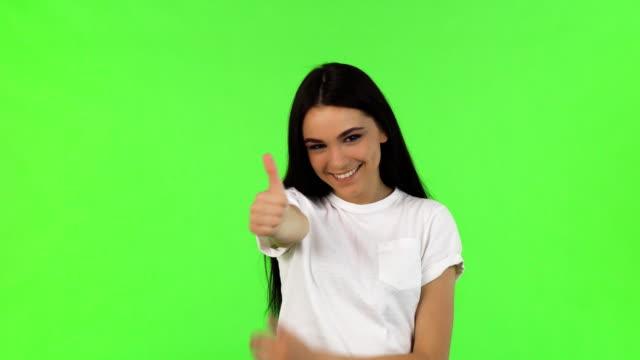 stockvideo's en b-roll-footage met gelukkig mooie vrouw duimen opdagen op groene achtergrond - wit t shirt