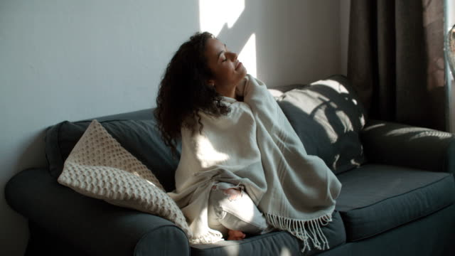 Happy beautiful woman sitting on sofa wrapped in blanket relaxing at home. Happy beautiful woman sitting on sofa wrapped in blanket relaxing at home. blanket stock videos & royalty-free footage
