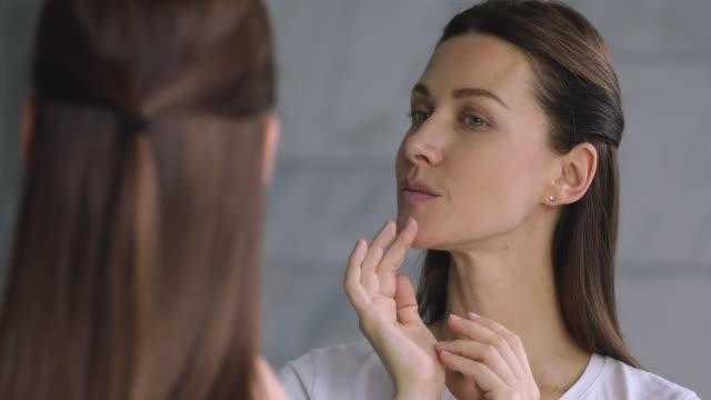 stockvideo's en b-roll-footage met gelukkig mooie jonge 30s vrouw aanraken gezicht kijken in spiegel - mirror mask