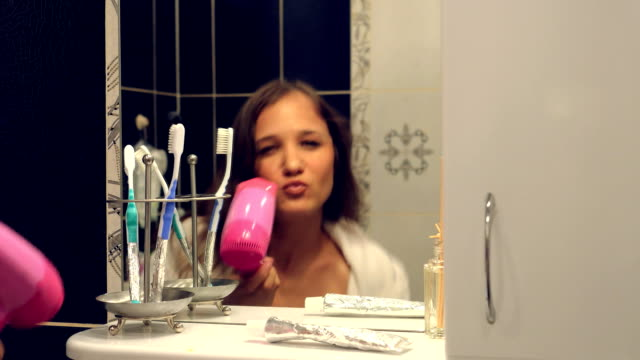 Happy beautiful young woman in a bathrobe singing and dancing in front of the bathroom mirror video