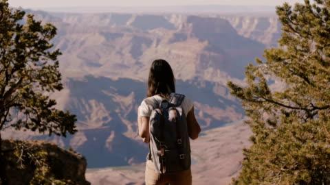 felice bella giovane donna con zaino che cammina fino allo straordinario scenario paesaggistico estivo del grand canyon al rallentatore. - canyon video stock e b–roll