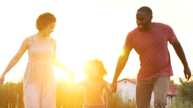 szczęśliwa dwurasowa rodzina spędzając razem czas i ciesząc się świeżym powietrzem w wiosce - happy holidays filmów i materiałów b-roll