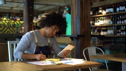 vídeos y material grabado en eventos de stock de propietario de negocio negro feliz del restaurante haciendo los libros utilizando una tableta y un bloc de notas - small business
