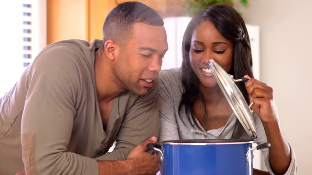 Happy black couple cooking in the kitchen video