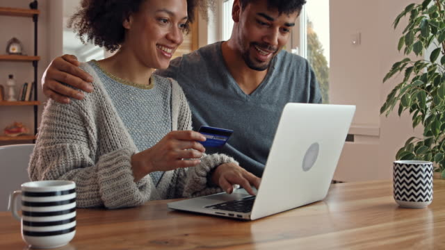 Happy black couple using credit card and laptop for online shopping at home. Young smiling African American couple home shopping with credit card and laptop. shopping online stock videos & royalty-free footage
