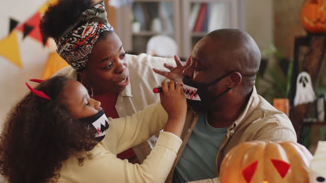 Happy Black Family Making Halloween Masks with Vampire Teeth Little African American girl drawing blood on vampire teeth mask of joyous dad with assistance of mother while making Halloween costumes at home together with family halloween covid stock videos & royalty-free footage