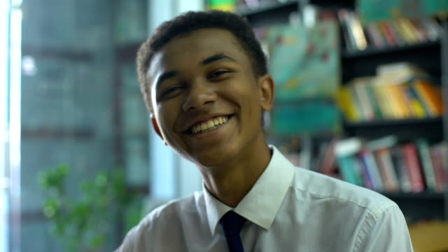 Happy black male student in uniform sincerely smiling on cam pleased with course