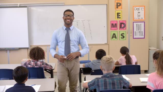 Happy black male teacher walking through class toward camera video