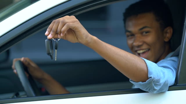 Happy black male teenager on driver place showing car keys, first automobile