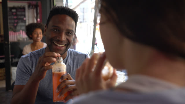 happy black man on a date at a juice bar with an unrecognizable woman talking while enjoying a juice - sok filmów i materiałów b-roll