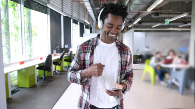 Happy black man putting on his headphones and listening to music while scrolling down his list on smartphone