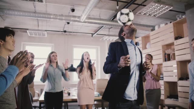 gärna svart teamledare jonglerar fotboll på huvudet. multietniskt start anställda fira framgång i office slow motion - sportaktivitet bildbanksvideor och videomaterial från bakom kulisserna