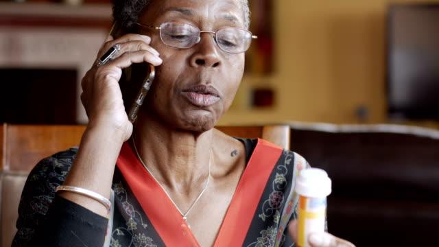 vídeos y material grabado en eventos de stock de feliz mujer negra completando su pedido de medicamentos recetados en su teléfono celular - receta instrucciones