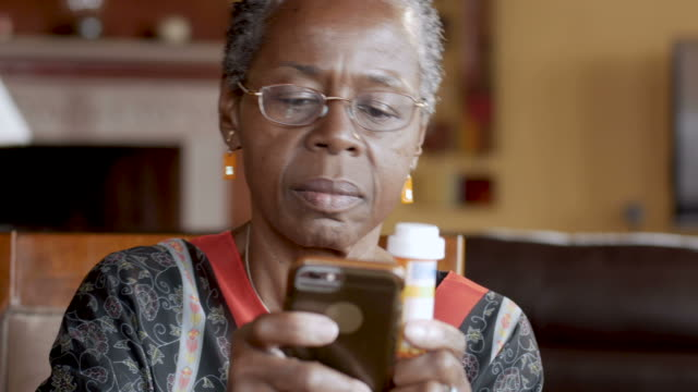 vídeos de stock e filmes b-roll de happy black woman refilling her prescription drugs online using a smart phone - medicare