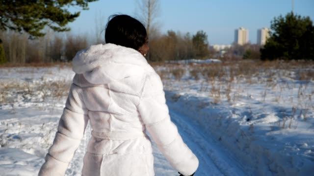happy black woman walks along snowy path in winter forest