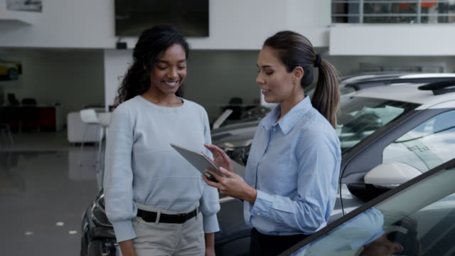 Happy black young woman closing a deal with saleswoman at a car dealership handshaking as she hands her the keys video