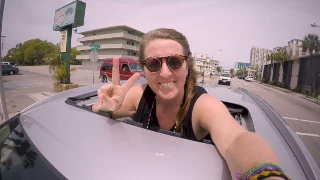 glücklich blonde frau, die immer selfie stehend durch ein sonnendach im auto - in den vierzigern stock-videos und b-roll-filmmaterial
