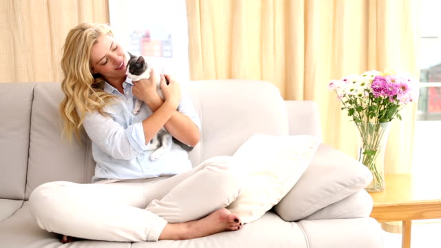 Happy blonde petting her kitten on the couch video