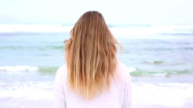 Glückliche blonde drehen und lächelnd in die Kamera am Strand – Video