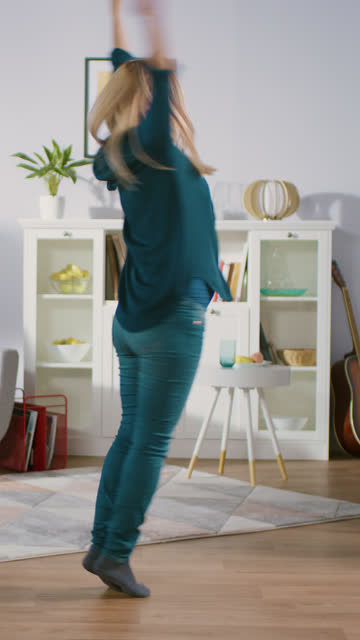 vídeos de stock e filmes b-roll de happy blonde woman dances in the middle of her living room. woman has fun home alone, dancing cheerfully. video footage with vertical screen orientation - vertical
