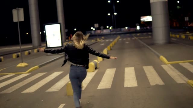 vídeos de stock e filmes b-roll de happy blonde woman having fun outdoors at the nighttime. running, immitating plane. wearing jeans and black jacket. rare view - young woman running city