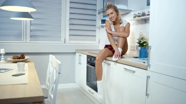 Happy blonde woman smiling at camera while sitting in the kitchen. video