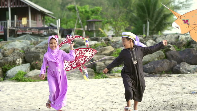 Happy boy and girl with kite and laughing boy running on the foreground. Happy boy and girl with a kite and laughing boy running on the foreground. middle east stock videos & royalty-free footage