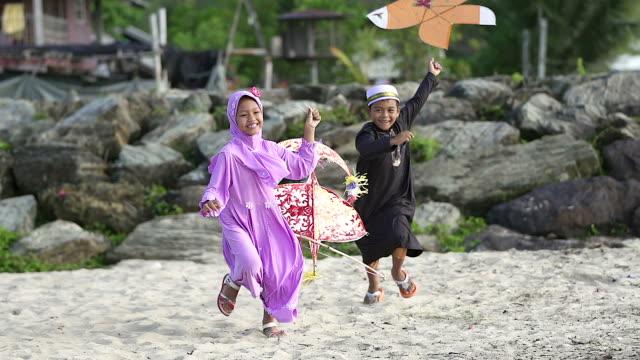 szczęśliwy chłopiec i dziewczyna z latawcem i śmiejącym się chłopcem biegającego na pierwszym planie. - islam filmów i materiałów b-roll