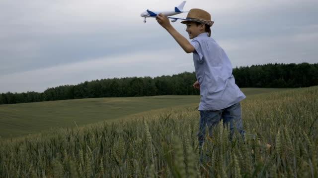 麦藁帽子の幸せな少年の夢を手に飛行機とフィールド間で実行します。 - 男の子点の映像素材/bロール