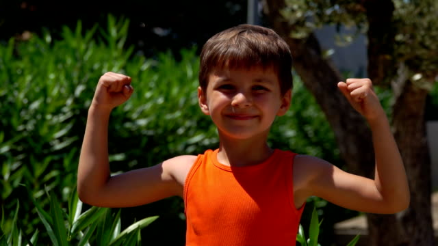 Happy boy in an orange shirt shows muscle - video