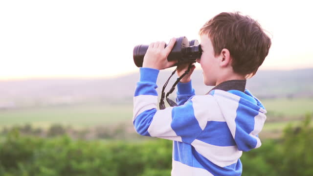 Happy boy is looking through the big binoculars a beautiful landscape of green hills at sunset of a sunny day slow motion and joyfully says something and shows by hand. Childhood