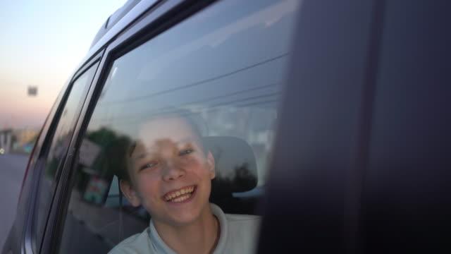 幸せな少年は車の後部座席に座って笑う。 ビデオ