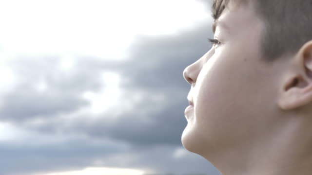 happy boy looks at the sky in windy weather close-up, bright light from the sky on the boy's face - guardare fisso video stock e b–roll