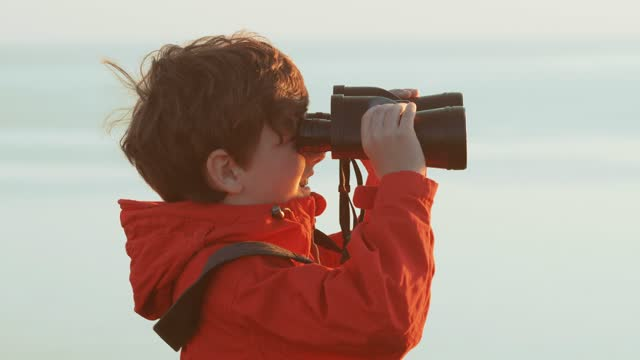 Happy boy looks through the big binoculars into the distance of the sea against the sunset of a sunny day, examines the commercial and passenger ships and joyfully says something