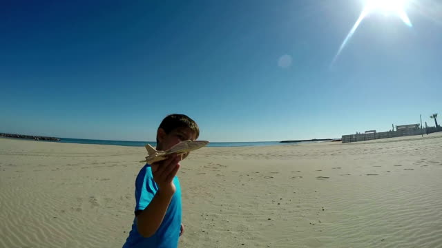 happy boy plays with model airplane on the beach - solo un bambino maschio video stock e b–roll