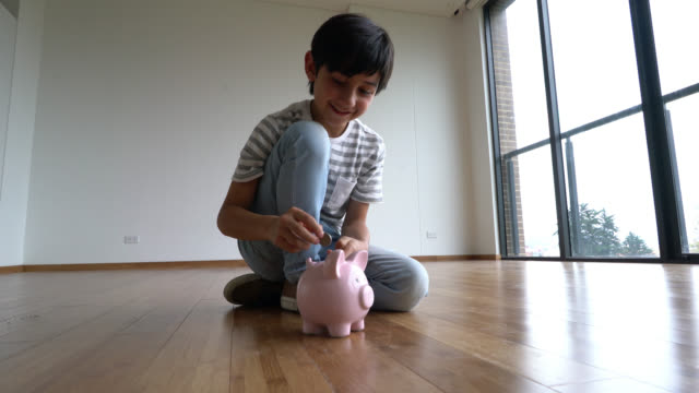 Happy boy putting coins in his piggy bank video