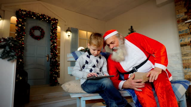 Happy boy receiving tablet from Santa Claus video