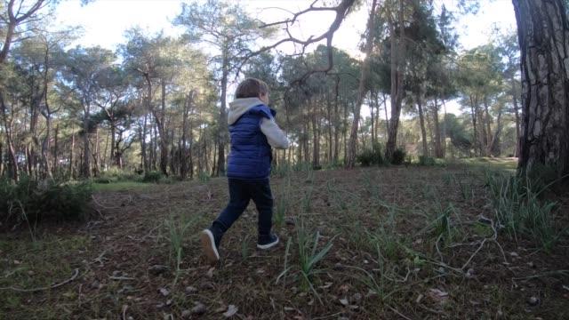 Happy boy running in forest