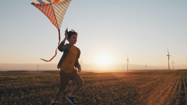 vídeos de stock, filmes e b-roll de happy boy corre lança pipa brilhante no campo de trigo do céu, brincando com o vento no campo de um pôr do sol laranja no dia lente sinaliza turbinas eólicas em câmera lenta de verão. pausa na escola. vida. infância - infância