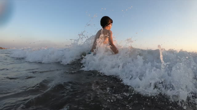 Happy boy swimming on the sea making splash