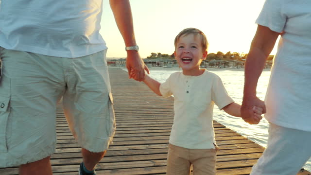 Happy boy walking with grandparents along the pier at sunset video