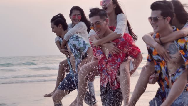 Happy boyfriends piggybacking their girlfriends and laughing together during summer holidays vacation on tropical beach.Vacations - iStock