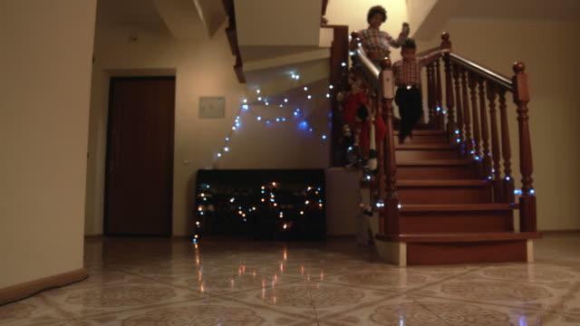 stockvideo's en b-roll-footage met gelukkige jongens rennen trap. - christmas tree